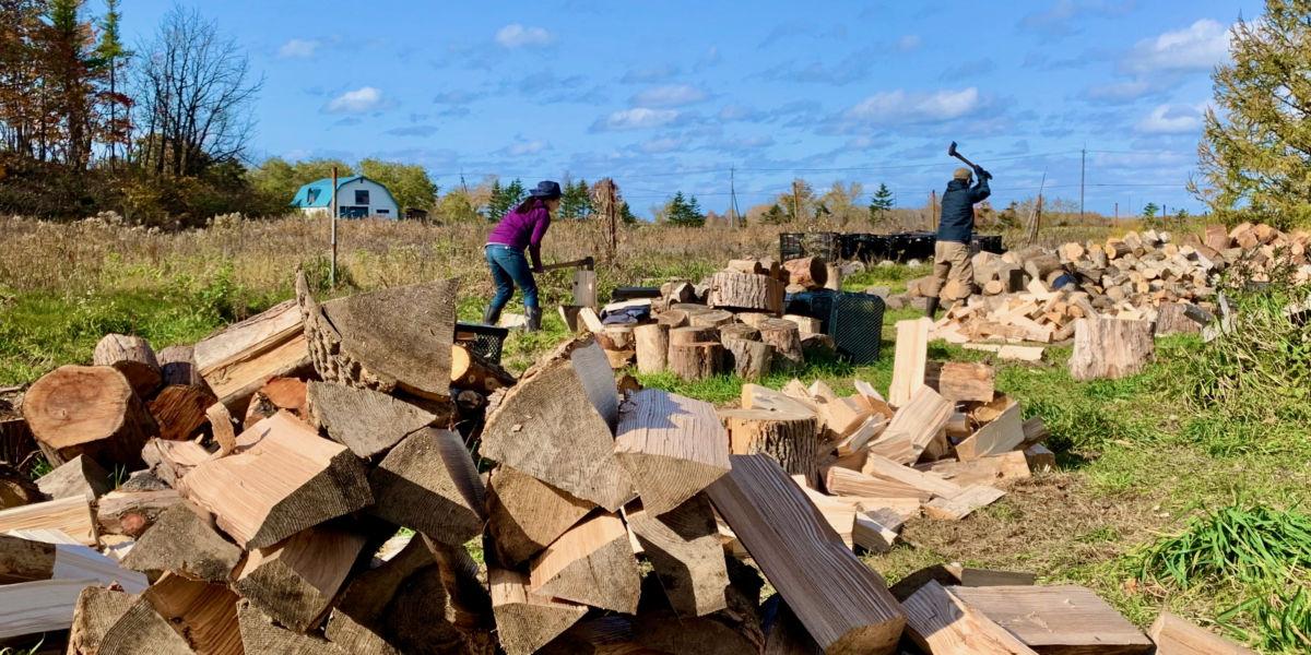 薪割りの現場。石狩にあるはるきちオーガニックファームの土地を借りて、年間100立米の薪を割ります。参加したボランティアは貸し出している安全靴や斧などを準備して、コーディネーターの指導のもと薪割りに夢中になる。